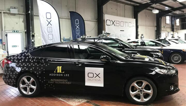 Picture of a fleet of autonomous cars with banners on the background.