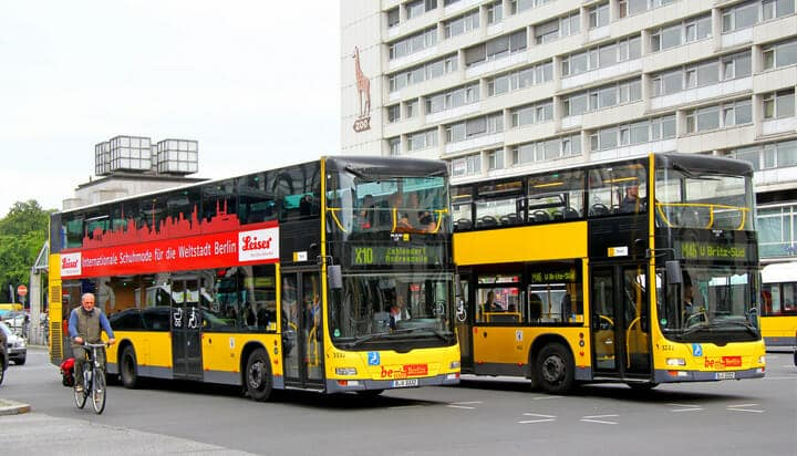 Picture of two yellow buses on the road in Berlin, Germany.