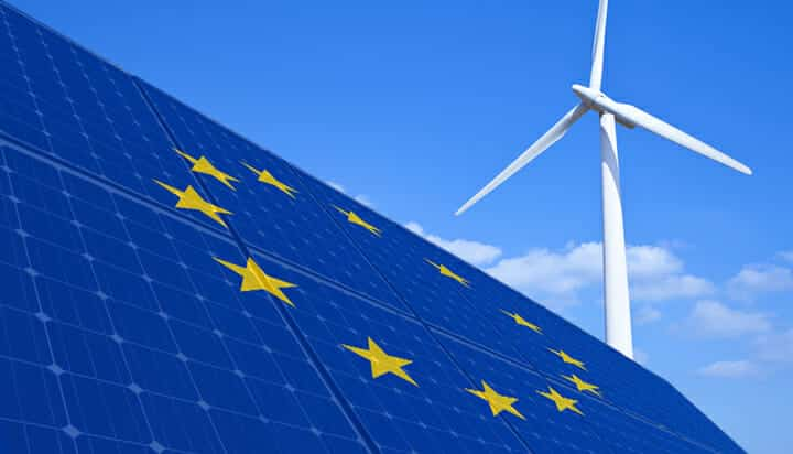 Picture of the European Union flag on solar panels and a wind turbine